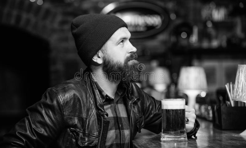 Hipster relaxing at pub. Man with beard spend leisure in dark pub. Brutal hipster relaxing. Guy bearded man sit at bar. Counter in pub. Weekend lifestyle. Pub stock photos