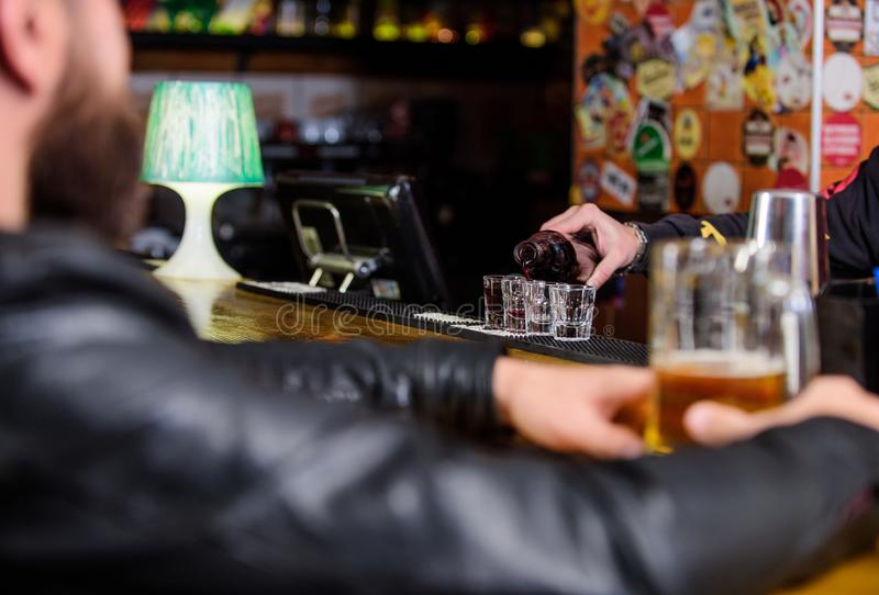Hipster relaxing at pub. Man spend leisure in dark pub. Man sit at bar counter in pub. Weekend lifestyle. Bartender. Pouring alcohol. Ordering drinks. Pub great stock images