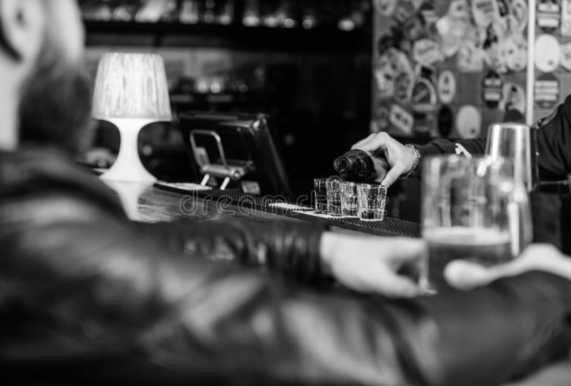 Hipster relaxing at pub. Man spend leisure in dark pub. Man sit at bar counter in pub. Weekend lifestyle. Bartender. Pouring alcohol. Ordering drinks. Pub great stock photo