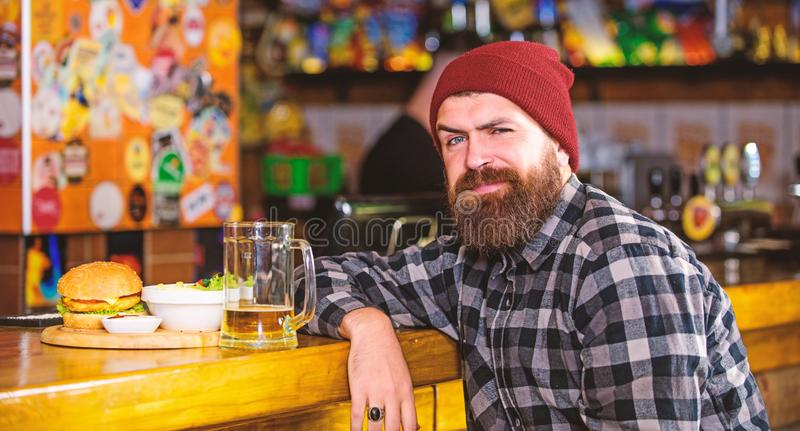 Hipster relaxing at pub. Pub is relaxing place to have drink and relax. Man with beard drink beer eat burger menu. Enjoy stock photo