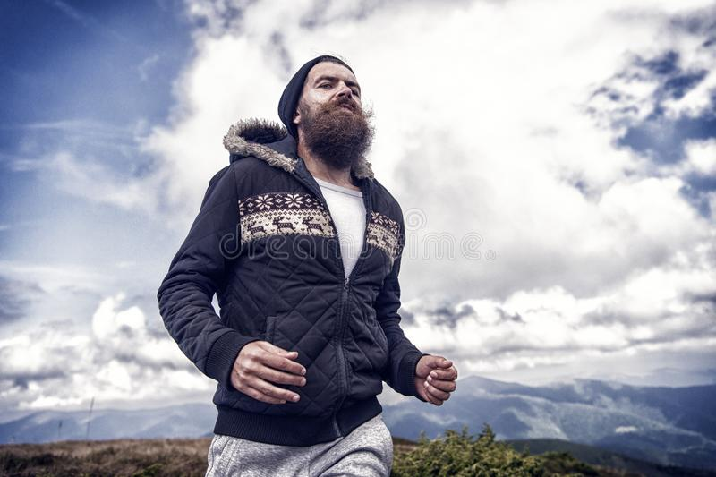 Hipster runner with long beard run on mountain landscape. On cloudy blue sky. Sport, energy, activity concept. Wanderlust, vacation, travel stock images