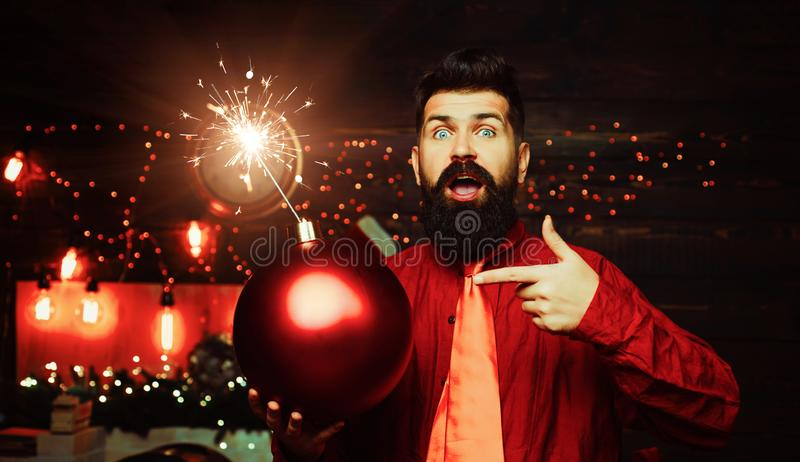 Hipster Santa claus. Christmas man in fashion red dress hold bomb. Creative boom. Hipster Santa claus. stock photography