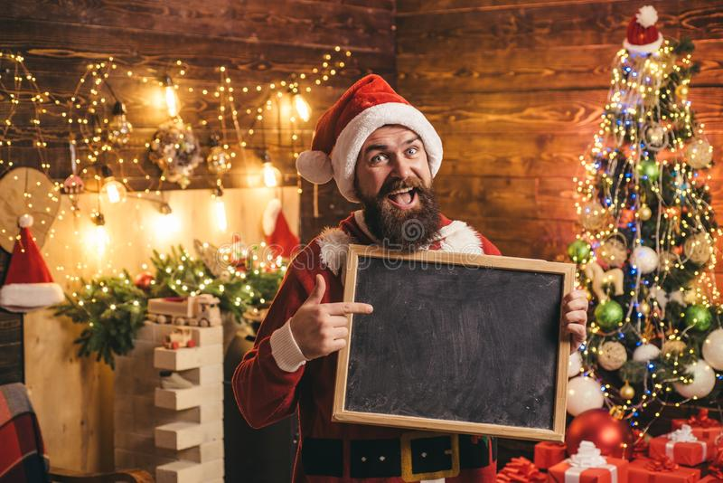 Hipster Santa with text board at home. Happy new year. Bearded man in Christmas sweater. Happy winter time. Funny Santa stock images