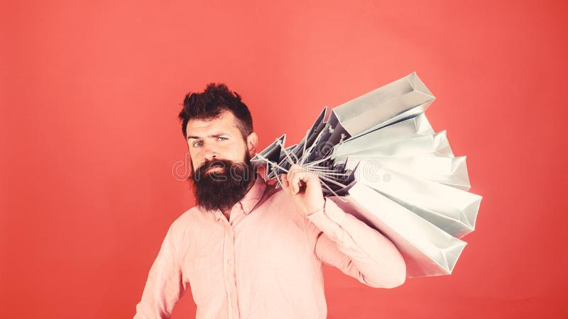 Hipster on sctrict face is shopping addicted or shopaholic. Guy shopping on sales season with discounts. Man with beard. And mustache carries shopping bags on royalty free stock image