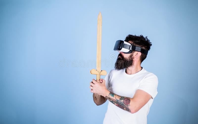 Hipster on serious face enjoy play game in virtual reality. Gamer concept. Man with beard in VR glasses, light blue royalty free stock photography