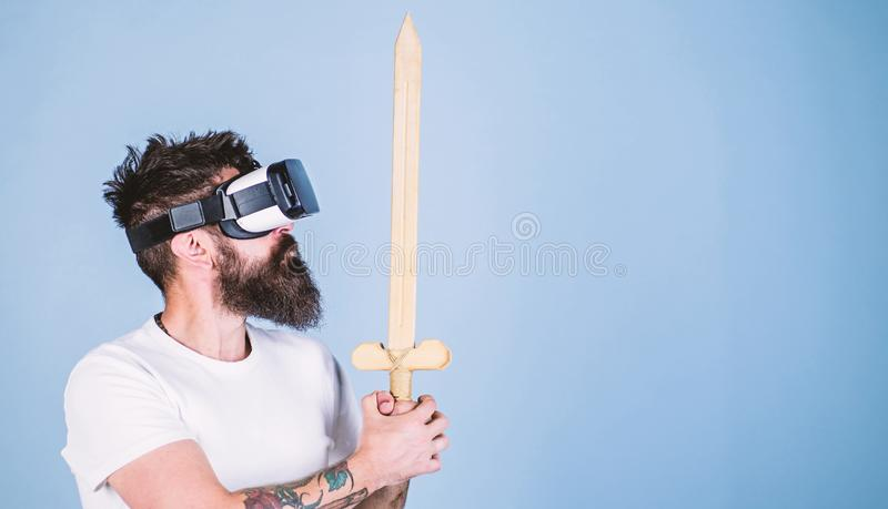 Hipster on serious face enjoy play game in virtual reality. Man with beard in VR glasses, light blue background. Gamer. Concept. Guy with head mounted display royalty free stock images
