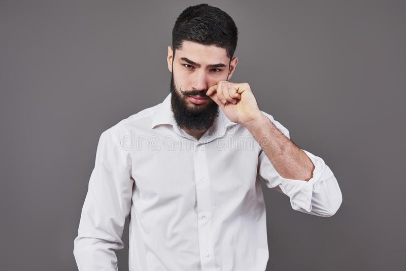 Hipster with serious face. Feeling and emotions. Guy or bearded man on grey background. Barber fashion and beauty. Man stock images