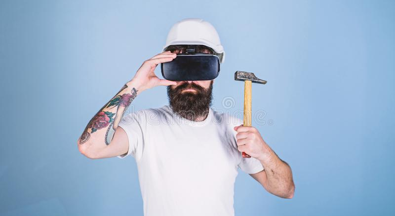 Hipster on serious face wear helmet, hold hammer in virtual reality. Virtual renovation concept. Man with beard in VR. Glasses hold hammer, light blue royalty free stock photo