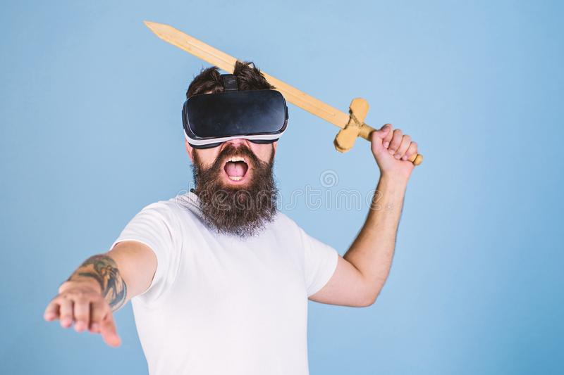 Hipster on shouting face enjoy play game in virtual reality. VR gamer concept. Man with beard in VR glasses, light blue stock photo