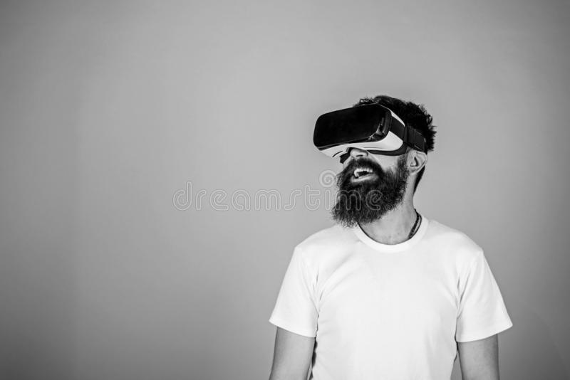 Hipster on smiling face enjoy virtual reality with gadget. Man with beard in VR glasses, light blue background. Digital stock photography