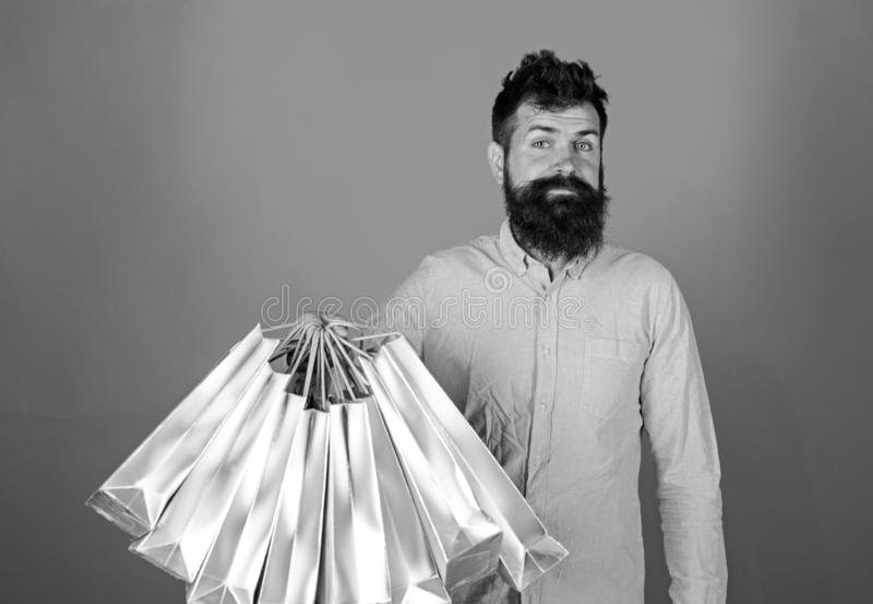 Hipster on smiling face is shopping addicted or shopaholic. Guy shopping on sales season with discounts. Man with beard. And mustache holds bunch of shopping royalty free stock photo