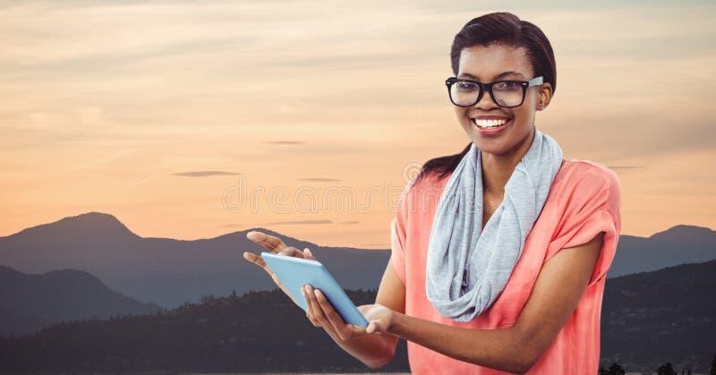 Hipster som rymmer den digitala minnestavlan, medan stå vid berg mot himmel arkivbild