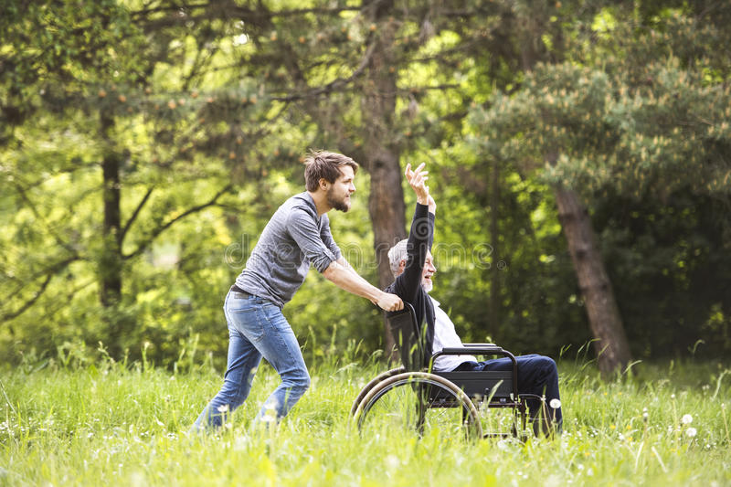 Hipster son walking with disabled father in wheelchair at park. royalty free stock images