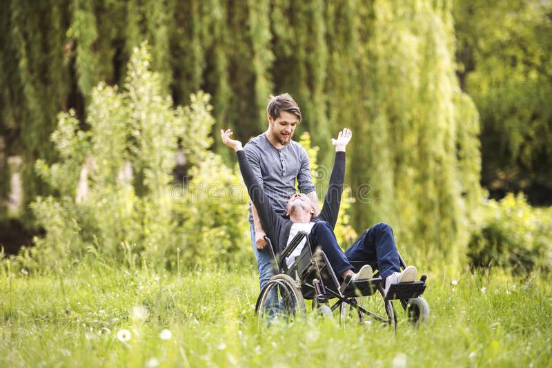 Hipster son walking with disabled father in wheelchair at park. stock photography