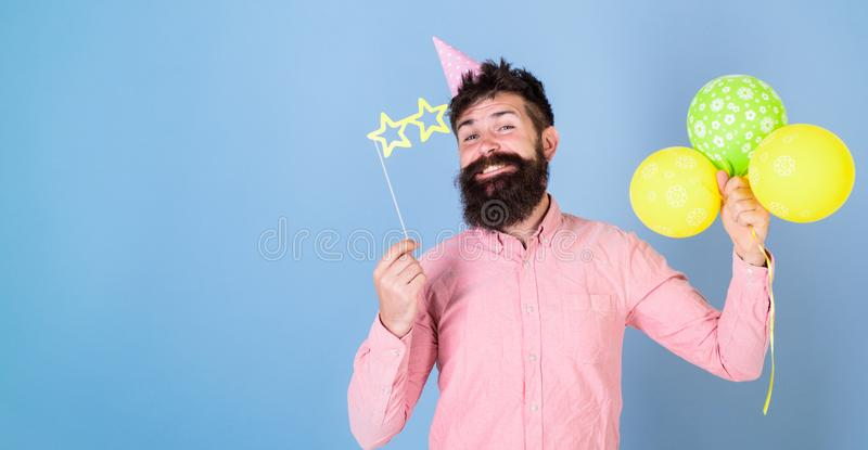 Hipster in star shaped glasses celebrates birthday. Party attributes concept. Guy in party hat with air balloons. Celebrates. Man with beard on happy face hold royalty free stock photos