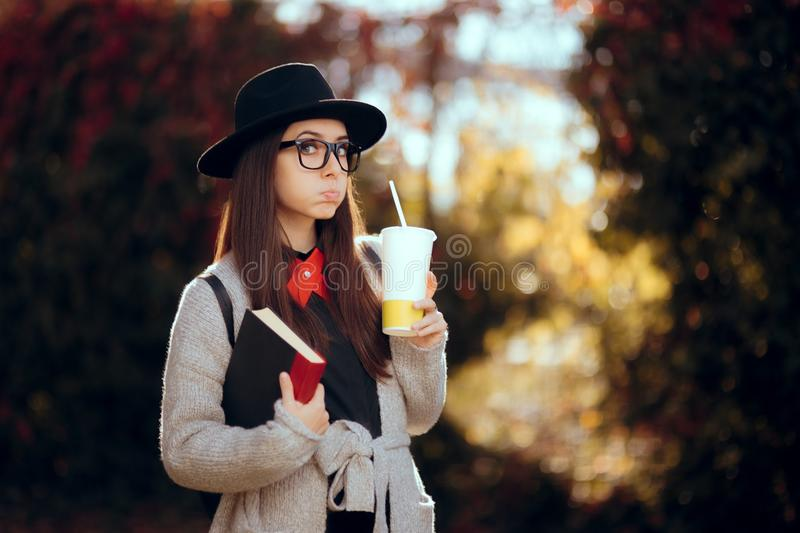 Hipster Student Holding a Book Outdoors in Autumn Decor royalty free stock images