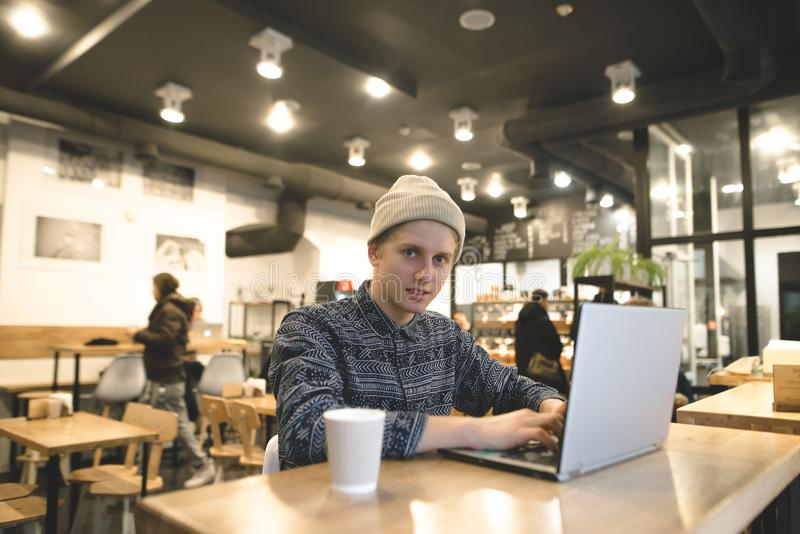 Hipster student sits in a cozy cafe with a laptop and works. A young man enjoys intranet on a laptop and drinks coffee. stock images