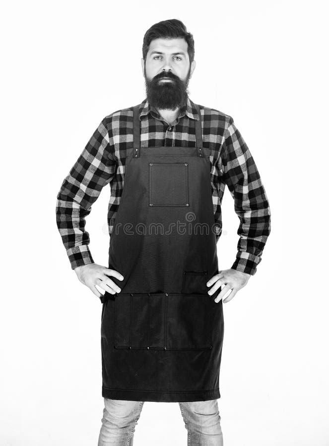 Hipster style. Barbershop concept. Hairdresser barber salon for men. Man brutal bearded hipster with mustache wear apron. Uniform. Barbershop staff. Beard stock photography