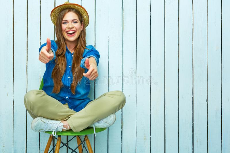 Hipster style woman full body portrait. Happy young woman show thumbs up. White plank background royalty free stock images