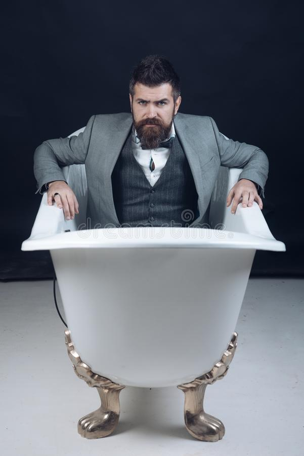 Hipster with stylish appearance in luxury old fashioned bathtub. royalty free stock image