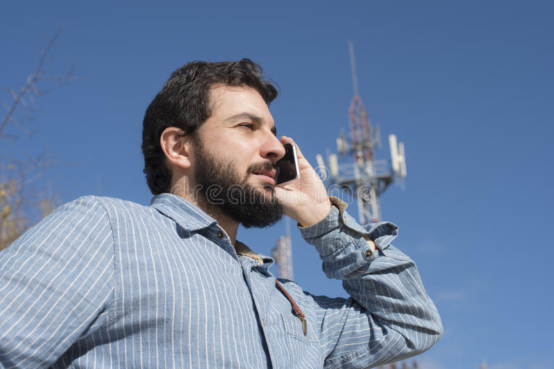 Hipster talking on phone next to an antenna of telecommunication. With sun light royalty free stock photo