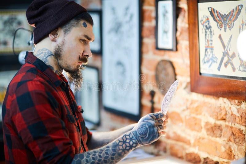 Hipster in tatoegering-salon stock fotografie