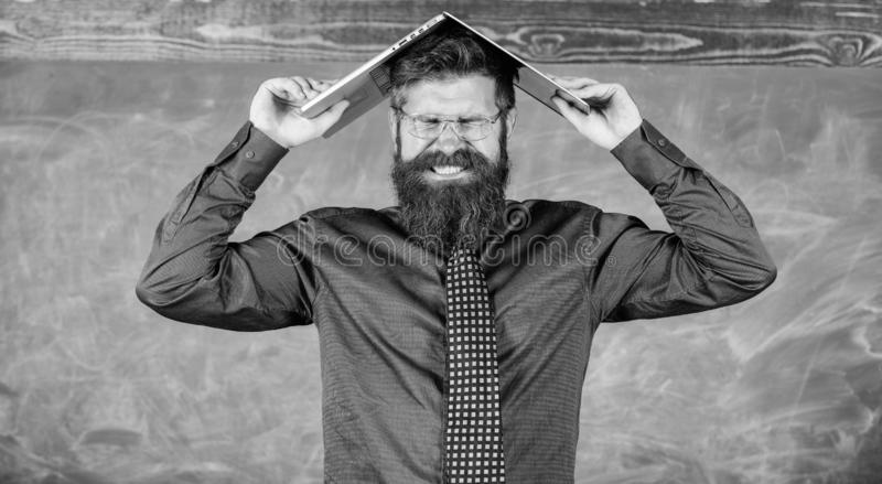 Hipster teacher aggressive with laptop as roof goes mad about teaching. Teacher bearded man with modern laptop. Chalkboard background. Can not get used to royalty free stock images