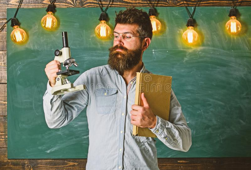 Hipster teacher with microscope, big blackboard. Man with beard and mustache on strict face in classroom. Scientific royalty free stock photo