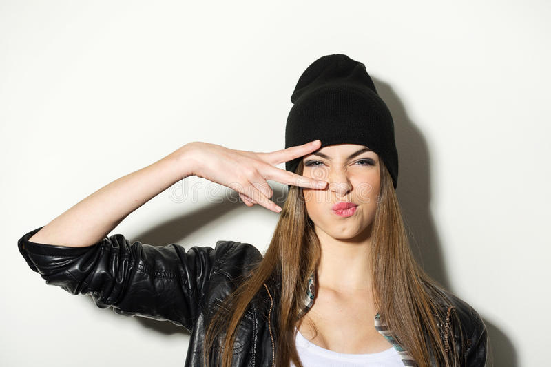 Hipster teenage girl with beanie hat posing. Hipster Caucasian teenage girl with black beanie hat posing making facial expression. Modern trendy young woman with royalty free stock images
