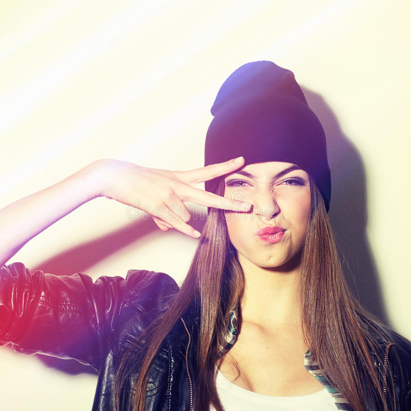 Hipster teenage girl with beanie hat pouting. Closeup studio shot of pretty hipster teenage girl with beanie hat pouting gesturing peace. Square image with royalty free stock image