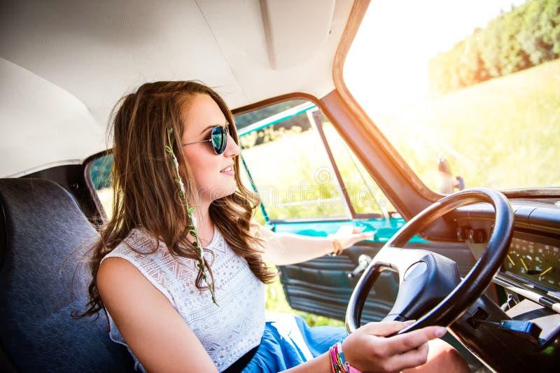 Hipster teenage girl inside an old campervan driving, roadtrip stock photo