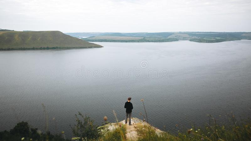Hipster teenager standing on top of rock mountain and looking on river, view from back. Atmospheric tranquil moment. Young guy. Exploring and traveling in stock photography