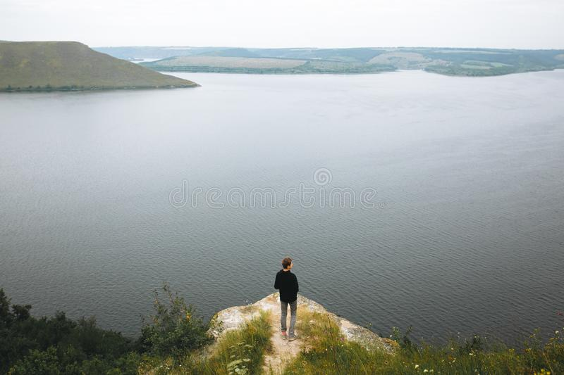 Hipster teenager standing on top of rock mountain and looking on river, view from back. Atmospheric tranquil moment. Young guy. Exploring and traveling in stock photos