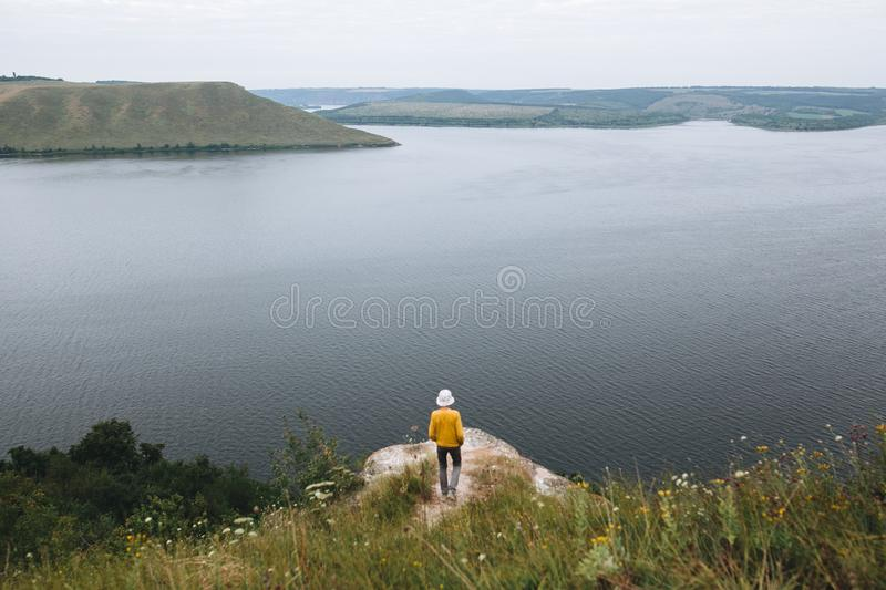 Hipster teenager standing on top of rock mountain and looking on river, view from back. Young stylish guy exploring and traveling. Atmospheric tranquil moment royalty free stock image