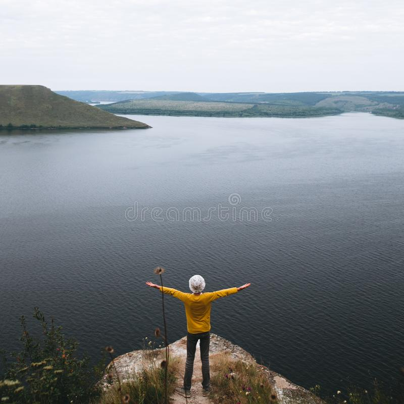 Hipster teenager in yellow pullover standing on top of rock mountain and looking on river, view from back. Young stylish guy. Exploring and traveling stock photography