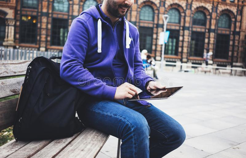 Hipster texting message on tablet computer or technology blank screen mockup. Smile young man using digital on building castle. Background. Male hands tourist stock photography