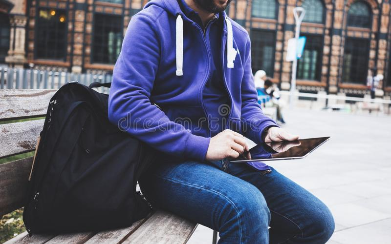 Hipster texting message on tablet computer or technology blank screen mockup. Smile young man using digital on building castle. Background. Male hands tourist royalty free stock image
