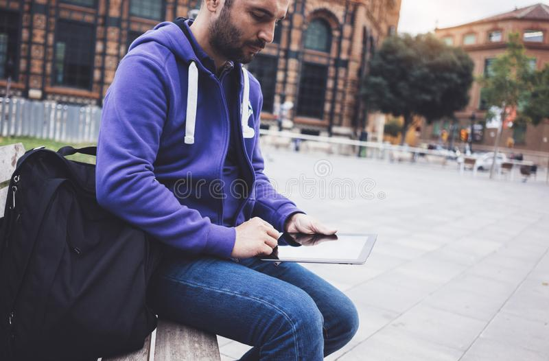 Hipster texting message on tablet computer or technology screen mockup. Smile young man using digital on building castle back. Ground. Male hands tourist holding stock photos