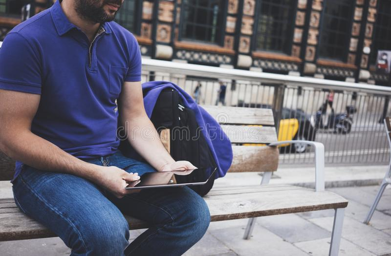 Hipster texting message on tablet computer or technology screen mockup. Smile young man using digital on building castle. Background. Male hands tourist holding royalty free stock photography