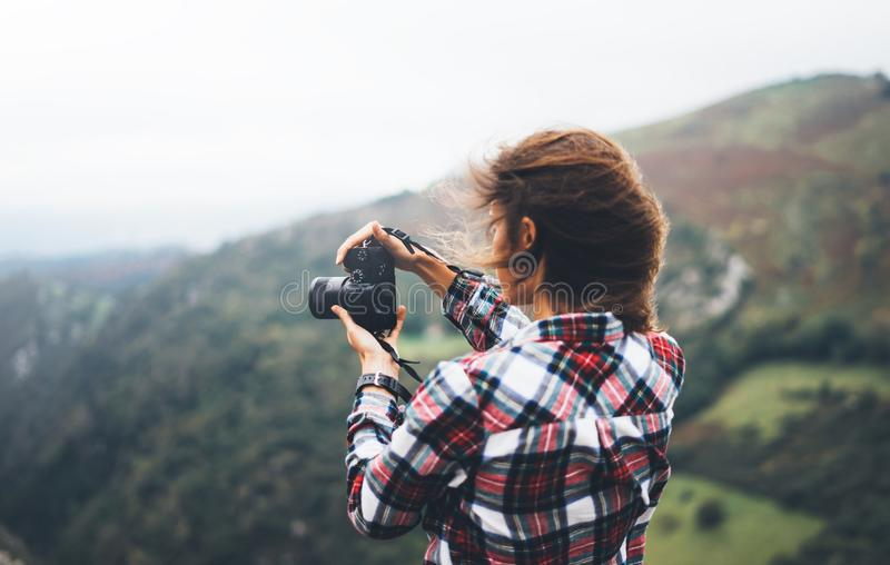 Hipster tourist girl hold in hands modern photo camera, photographer look on camera technology take photography click, journey. Landscape vacation concept, wind royalty free stock photos