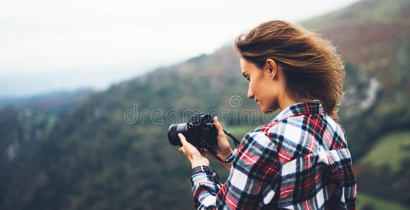 Hipster tourist girl hold in hands modern photo camera, photographer look on camera technology take photography click, journey. Landscape vacation concept, wind stock image