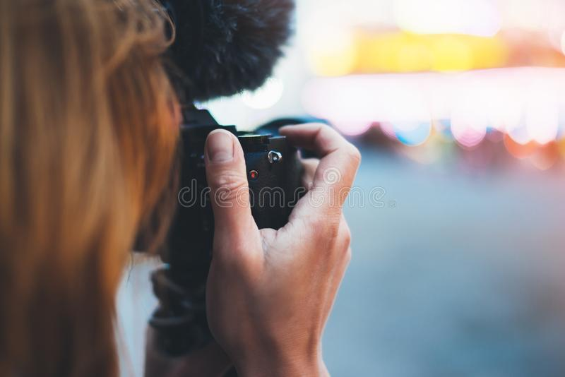 Hipster tourist girl hold in hands modern photo camera, take photography click on defocus background bokeh light in evening street. Attraction, photographer stock images