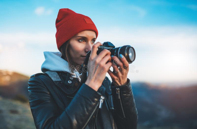 Hipster tourist girl hold in hands take photography click on modern photo camera, photographer look on camera technology, journey. Landscape vacation concept royalty free stock image
