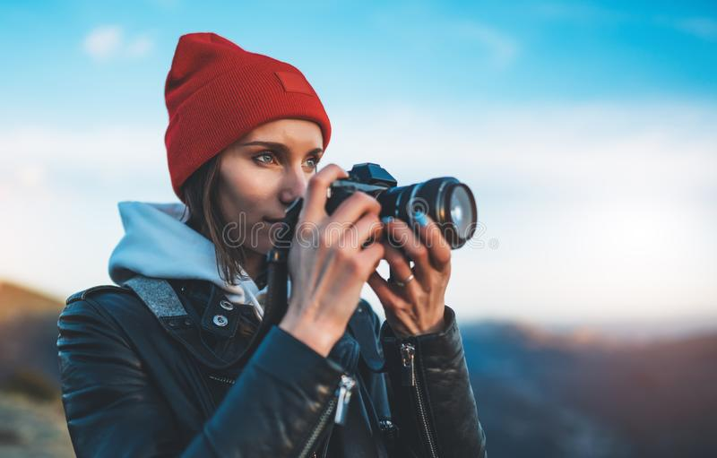 Hipster tourist girl hold in hands take photography click on modern photo camera, photographer look on camera technology, journey. Landscape vacation concept stock image