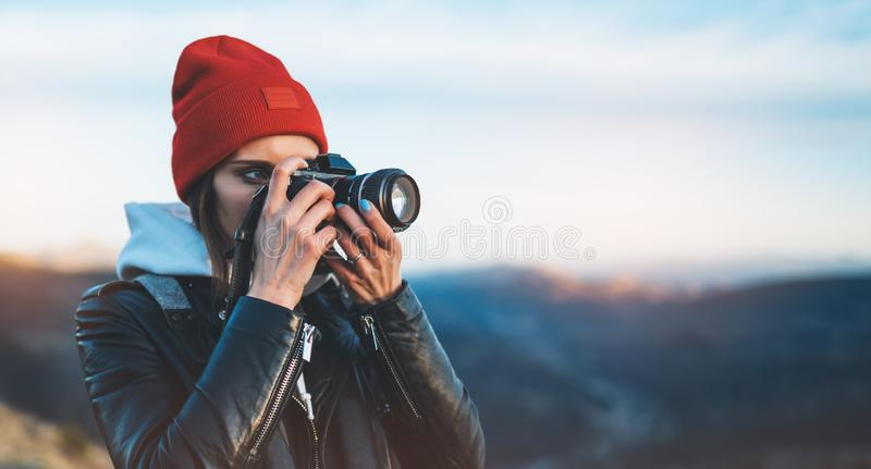 Hipster tourist girl hold in hands take photography click on modern photo camera, photographer look on camera technology, journey. Landscape vacation concept royalty free stock photos