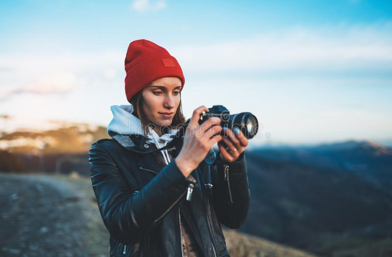 Hipster tourist girl hold in hands take photography click on modern photo camera, photographer look on camera technology, journey. Landscape vacation concept stock photos
