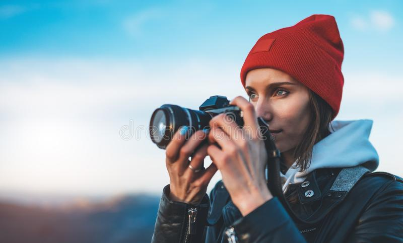 Hipster tourist girl hold in hands take photography click on modern photo camera, photographer look on camera technology, journey. Landscape vacation concept royalty free stock images