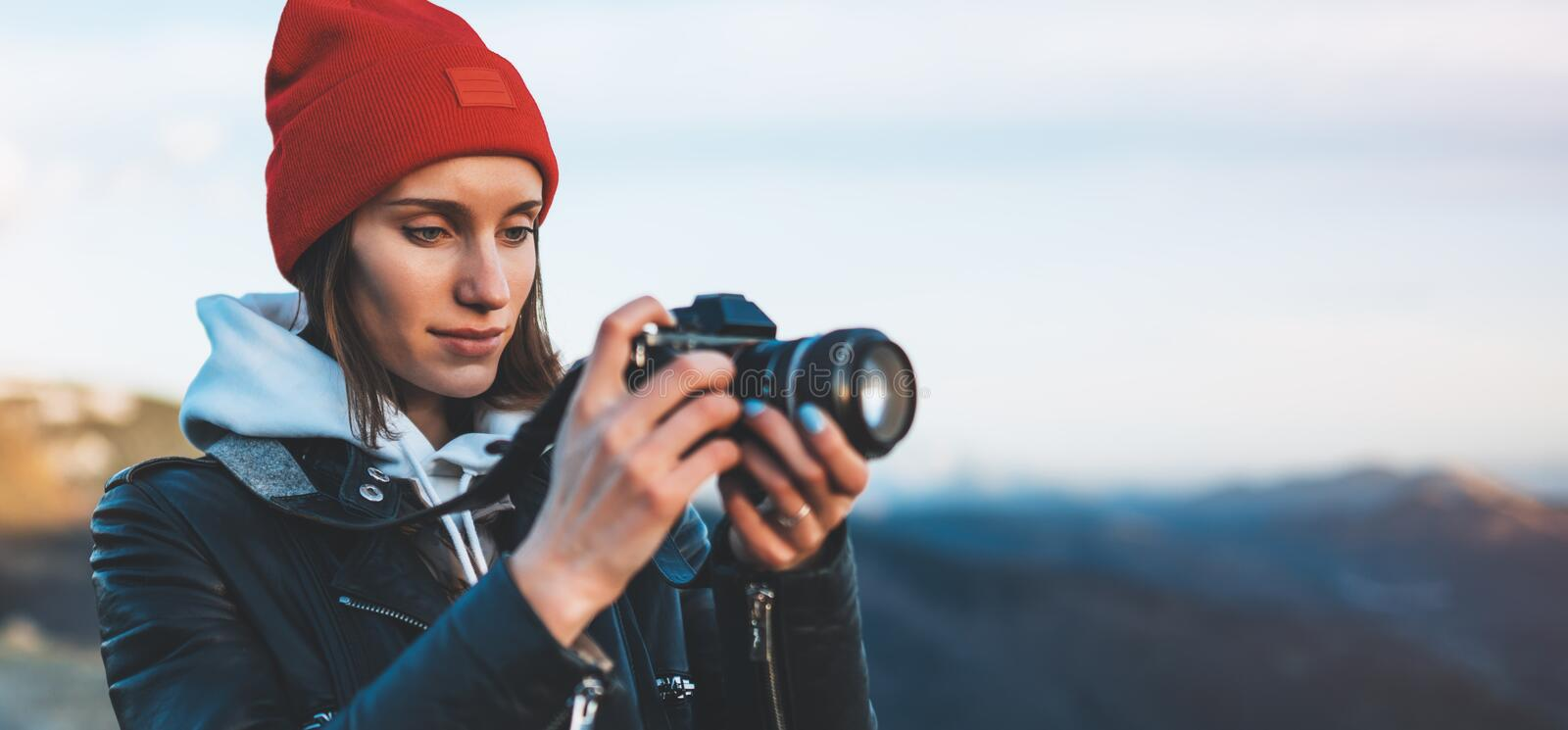 Hipster tourist girl hold in hands take photography click on modern photo camera, photographer look on camera technology, journey. Landscape vacation concept stock photo