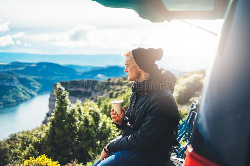 Hipster tourist hold in hands mug of hot drink, lonely guy enjoy sun flare mountain in auto, happy traveler drink cup of tea. On nature, vacation weekend stock photo