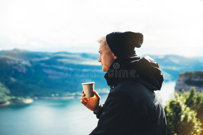 Hipster tourist hold in hands mug of hot drink, lonely guy enjoy sun flare mountain in auto, happy traveler drink cup of tea. On nature, vacation weekend royalty free stock photo